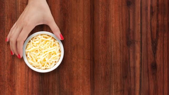 offering grated cheese - sfondo marrone video stock e b–roll