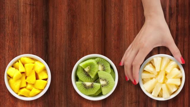 vidéos et rushes de offrant des fruits tropicaux - aliment en portion