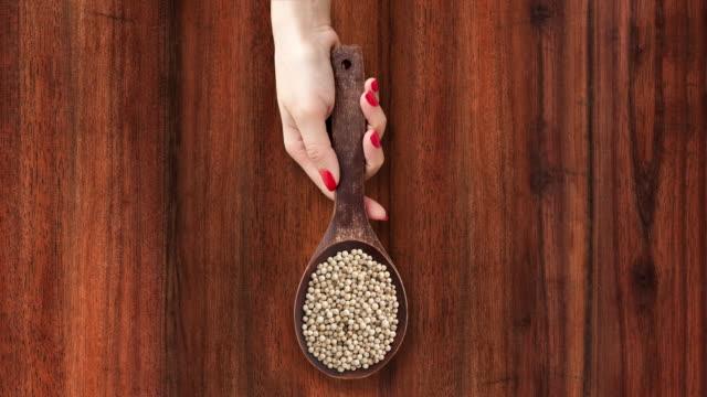 offering white peppercorns - sfondo marrone video stock e b–roll