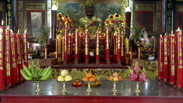 Offerings and candles burn on an altar in a Chinese temple