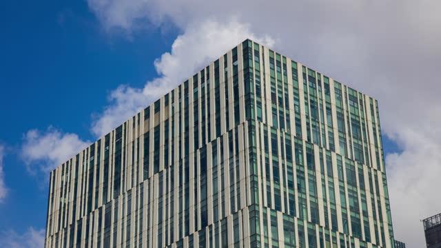 office building and cloud reflection 4k tight shot attractive office building timelapse background with fast moving cloud. - fönsterrad bildbanksvideor och videomaterial från bakom kulisserna
