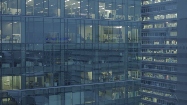office building at night with office workers working late - office block exterior stock videos & royalty-free footage