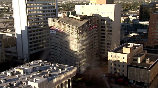 vidéos et rushes de ws office building in middle of  city is demolished in  controlled implosion using explosives / midland, texas, usa - imploding