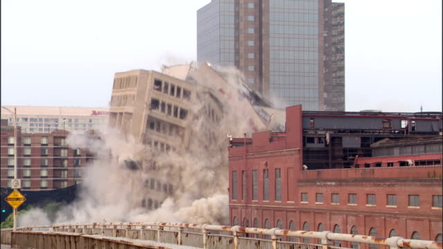 WS Office building in the middle of the city is demolished in  controlled implosion using explosives creating huge dust cloud / Louisvile, Kentucky, USA