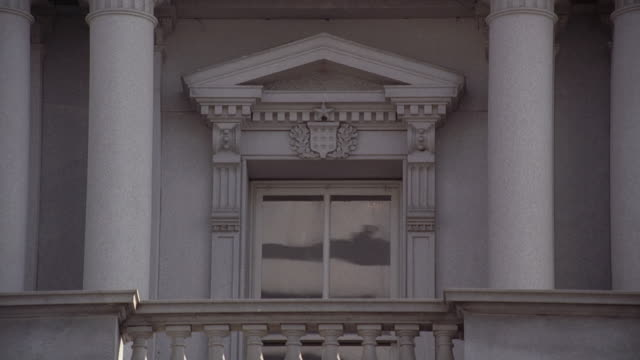 zo office building window surrounded by ornate pediment overlooking a balcony with stone railing and columns on either side / washington, district of columbia, united states - ペディメント点の映像素材/bロール