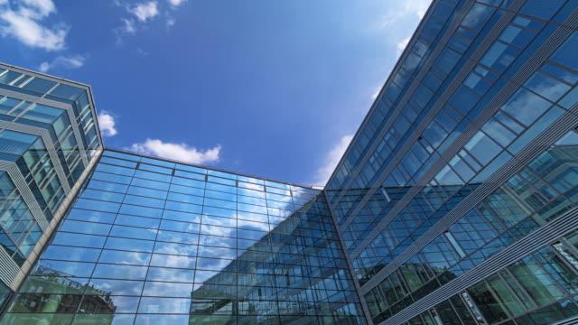 bürogebäude mit glasfassade und reflexion der wolken - österreich stock-videos und b-roll-filmmaterial