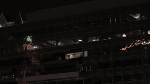 la office building with light shining through some windows at night, and one light turning on / philadelphia, pennsylvania, united states - turning on or off stock videos & royalty-free footage
