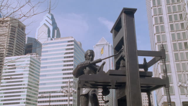 office buildings look down on a statue of benjamin franklin operating a printing press. - benjamin franklin stock videos & royalty-free footage