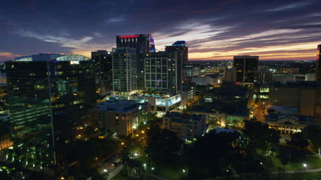 office buildings on the shore of lake eola in orlando at dusk - aerial - gulf coast states stock videos & royalty-free footage