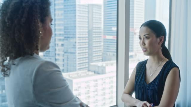 office-konversation. asiatisk affärskvinna pratar med sin kollega - fönsterrad bildbanksvideor och videomaterial från bakom kulisserna