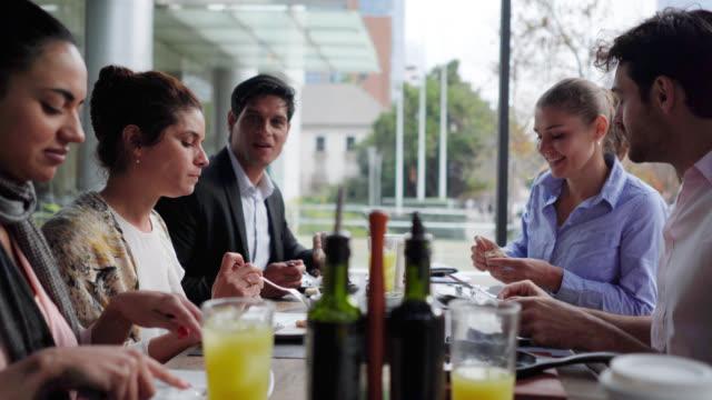 vidéos et rushes de amis de bureau appréciant un déjeuner délicieux ensemble parlant et souriant - déjeuner
