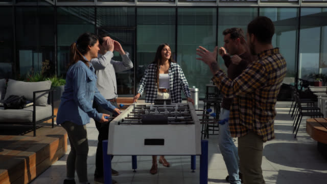 office friends playing foosball at the terrace celebrating a score while other look disappointed - lifestyles - recreational pursuit stock videos & royalty-free footage
