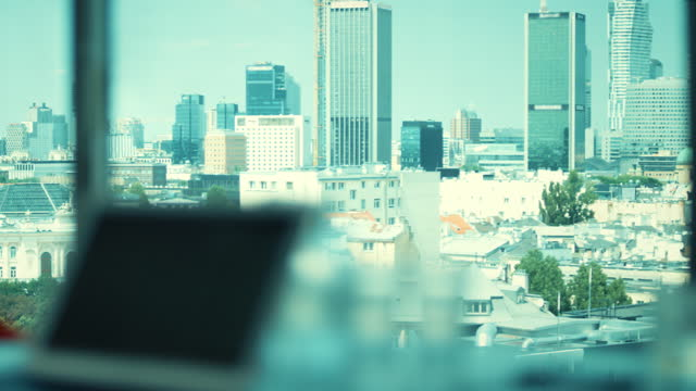office interior with a view. blurred foreground with laptop on a desk - office chair stock videos & royalty-free footage