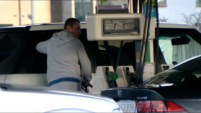 office of fair trading reviews petrol prices as 'fair' car along past petrol station man filling up van with unleaded fuel sajid javid mp interview... - unleaded stock videos and b-roll footage