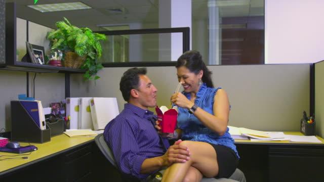 vídeos y material grabado en eventos de stock de ms office romance, man and woman sitting in office and eating takeout food, austin, texas, usa - en el regazo