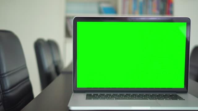 vidéos et rushes de coup de bureau vert projeté écran d'ordinateur portable sur le bureau - modèle réduit