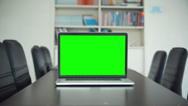 office skott av grön screening laptop skärm på skrivbord - oskriven bildbanksvideor och videomaterial från bakom kulisserna