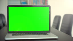 Office shot of green screened laptop screen on desk,Dolly shot