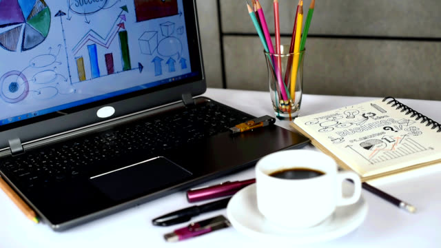 Office table with laptop, analyzing graphic, notebook, cup of coffee / business conceptual