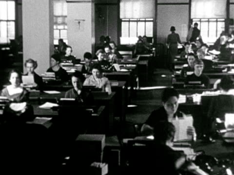 vídeos de stock e filmes b-roll de office w/ men at tables counting small stacks of paper, rows of desks w/ women working at typewriters, envelopes handed to women at desk, reverse... - instrumento de escrita