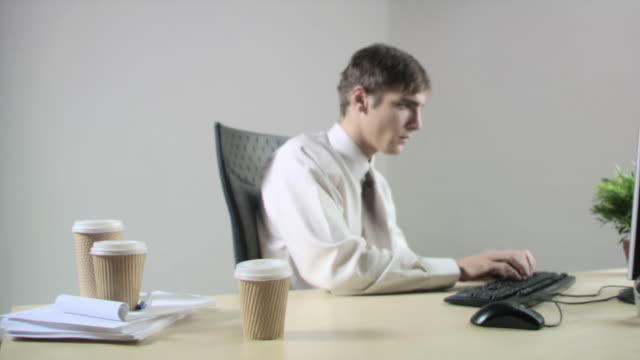 Office worker at desk knocking coffee cup over