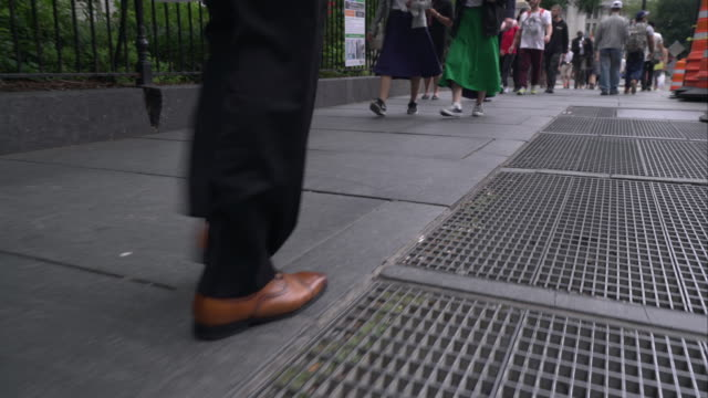 Office worker in business shoes walks on subway grate on New York City sidewalk.