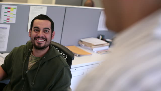 office worker in cubicle chats, laughs with friend - content stock videos and b-roll footage