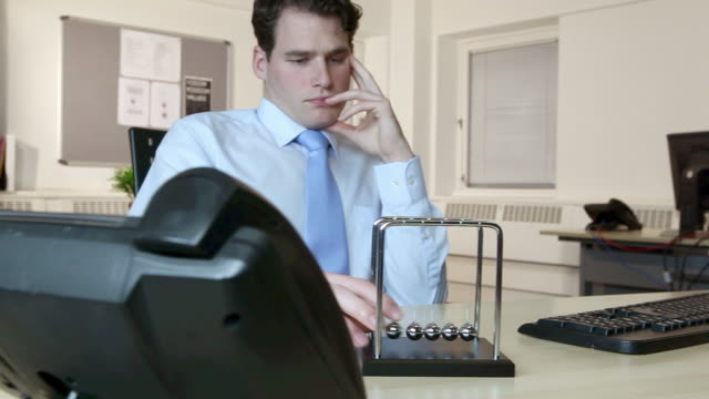 office worker playing with newtons cradle - spielzeug stock-videos und b-roll-filmmaterial