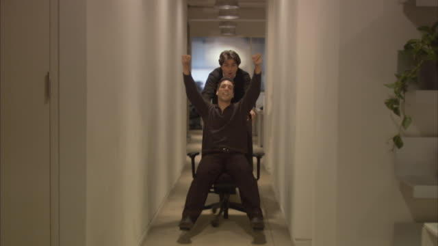 Office worker pushing colleague in chair in office corridor, laughing / New York City, New York, USA