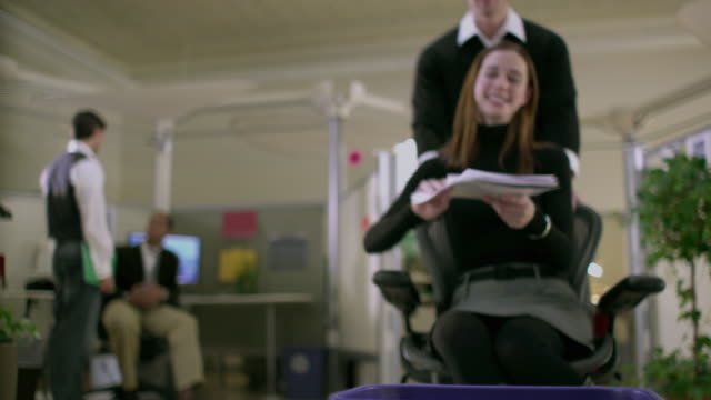 ms td cu selective focus office worker pushing colleague in office chair holding piece of paper towards recycle basket, appleton, wisconsin, usa - office chair stock videos & royalty-free footage