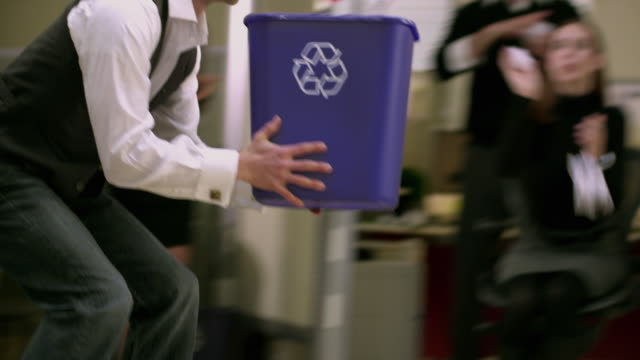 MS PAN Office worker rollerblades by cubicles holding recycle basket, colleagues throwing paper pieces at him, Appleton, Wisconsin, USA
