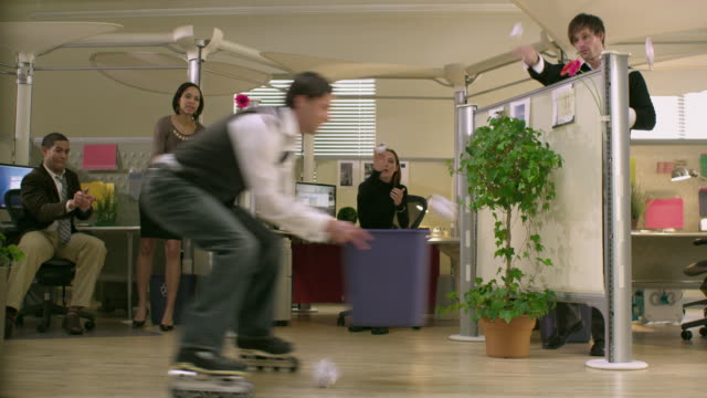 ms office worker rollerblades by cubicles holding recycle basket, colleagues throwing paper pieces at him, appleton, wisconsin, usa - spaß stock-videos und b-roll-filmmaterial
