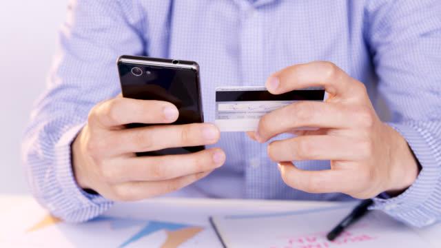 vídeos de stock, filmes e b-roll de trabalhador de escritório ds compras on-line com telefone inteligente - gastando dinheiro