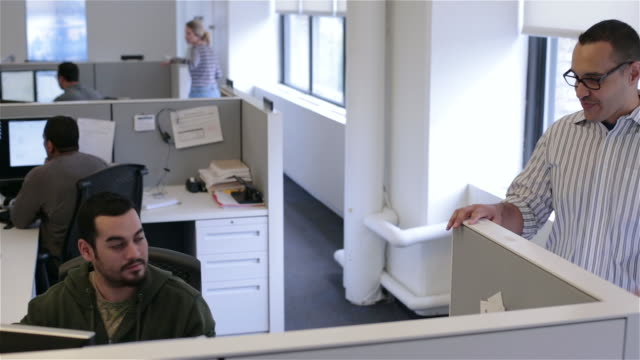 Office worker types on computer, friend stops by cubicle to chat (dolly shot)