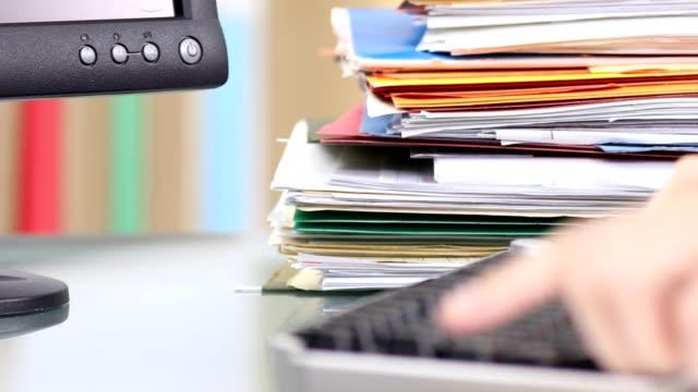 stockvideo's en b-roll-footage met kantoorbediende te typen op het toetsenbord, stack van mappen. - personeelsbeleid