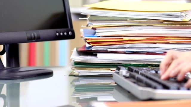 フォルダーのスタック コンピューターのキーボードで入力する事務員。 - 沢山の物点の映像素材/bロール