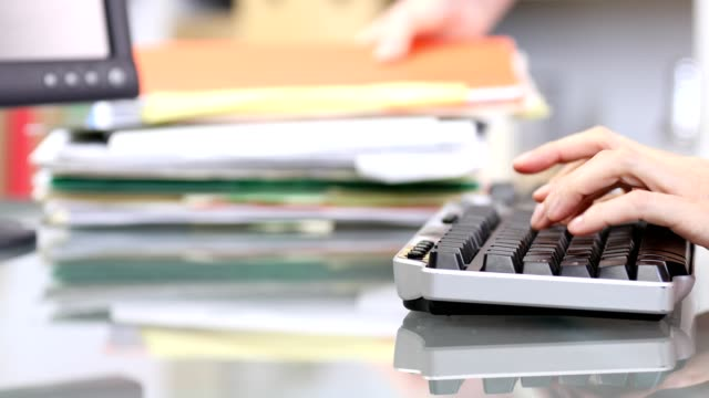 office worker typing on computer keyboard, stacking files. - excess stock videos & royalty-free footage