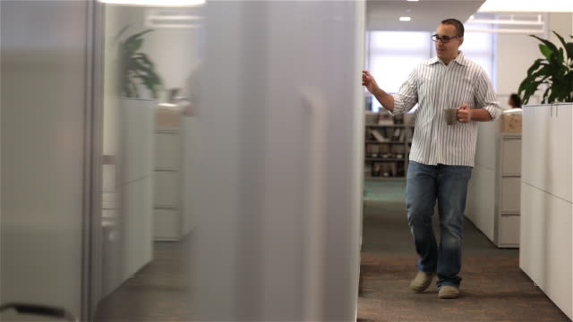 Office worker with coffee mug walks down hall, stops in doorway to chat (dolly shot)