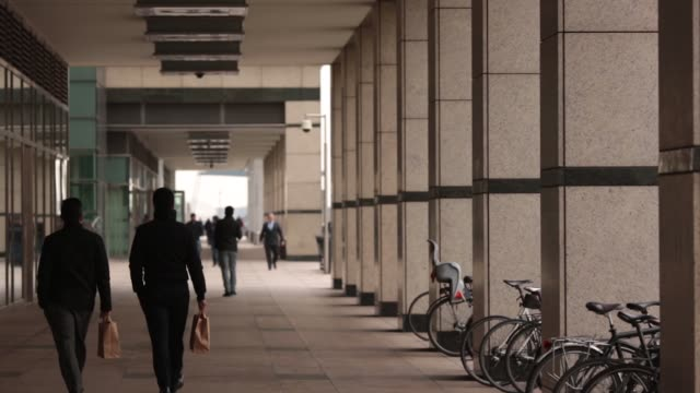 office workers and pedestrians walk along a street in the canary wharf business financial and shopping district of london uk on friday dec 5 back... - colonnade stock videos & royalty-free footage
