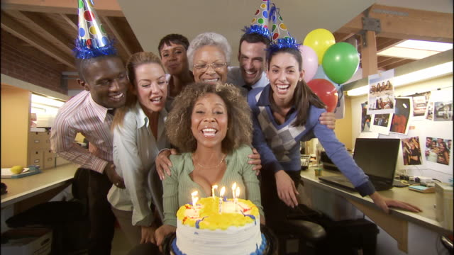 MS Office workers holding birthday cake and cheering toward camera in office decorated with balloons / Los Angeles, California, USA