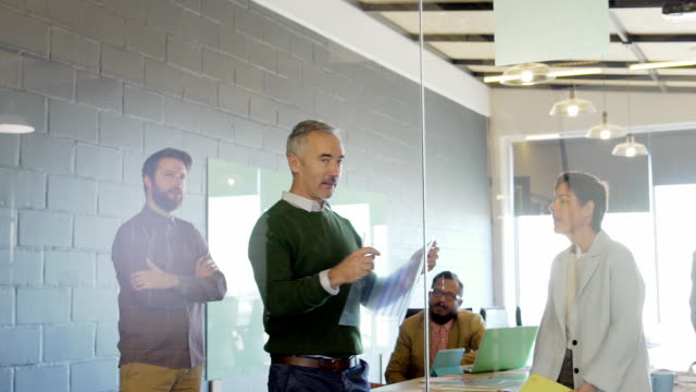 Office workers in meeting man placing graph on glass partition