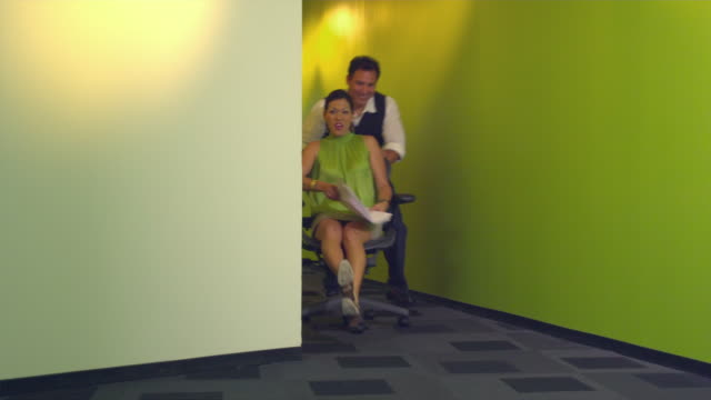 MS Office workers joking around office pushing desk chair, Austin, Texas, USA