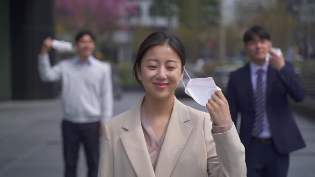 office workers on the way to workplace smiling while taking off a protective mask to prevent covid-19 / seoul, south korea - rimuovere video stock e b–roll