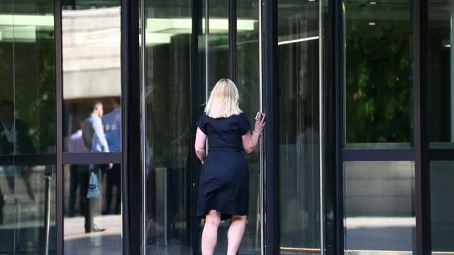office workers pass through a revolving door.  - revolving door stock videos & royalty-free footage