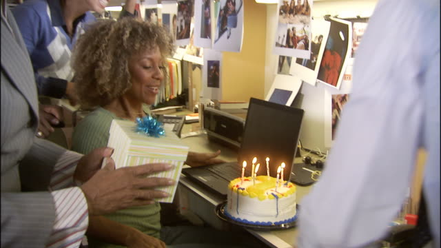 vídeos de stock, filmes e b-roll de ms zi cu office workers surprising woman with birthday cake, balloons and gift and she blows out candles / los angeles, california, usa - aniversário