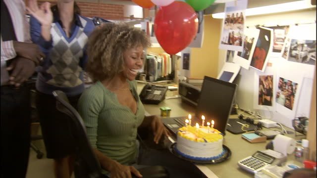 ms zi cu office workers surprising woman with birthday cake, balloons and gift and she blows out candles / los angeles, california, usa - birthday gift stock videos & royalty-free footage