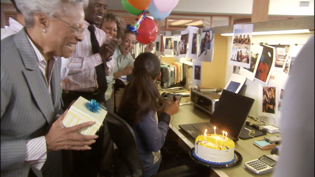ms zi zo office workers surprising woman with birthday cake, balloons and gift and she blows out candles / los angeles, california, usa - arbeitsstätten stock-videos und b-roll-filmmaterial