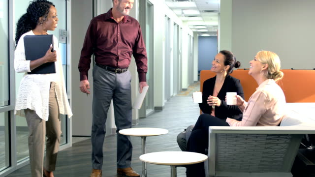 Office workers walk down hallway, greet coworkers