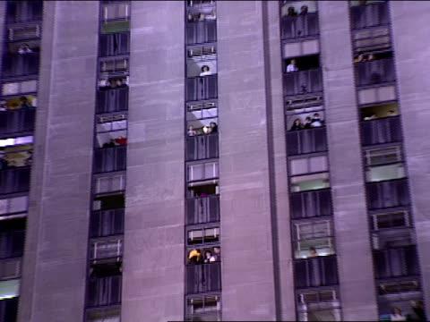 stockvideo's en b-roll-footage met office workers watching from high floor windows of 30 rockefeller plaza zo td ws lighted tree in rockefeller plaza - verlichtingsceremonie kerstboom