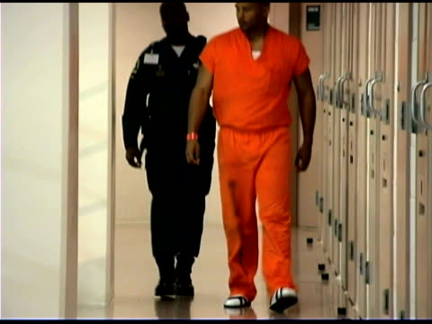 Officer and prisoner walking in prison
